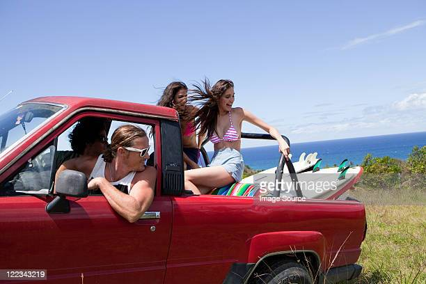 Four young friends driving off road vehicle on vacation