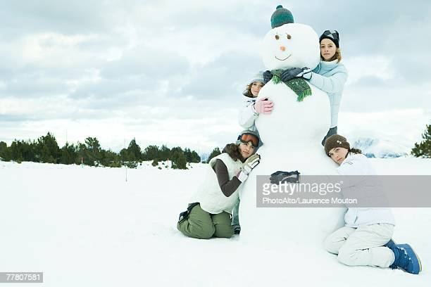 Four young friends embracing snowman, group portrait, one looking at camera
