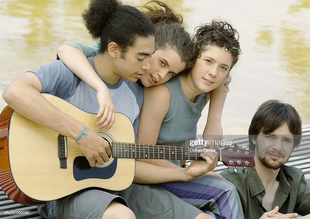 Four young friends gathered around guitar : Stockfoto