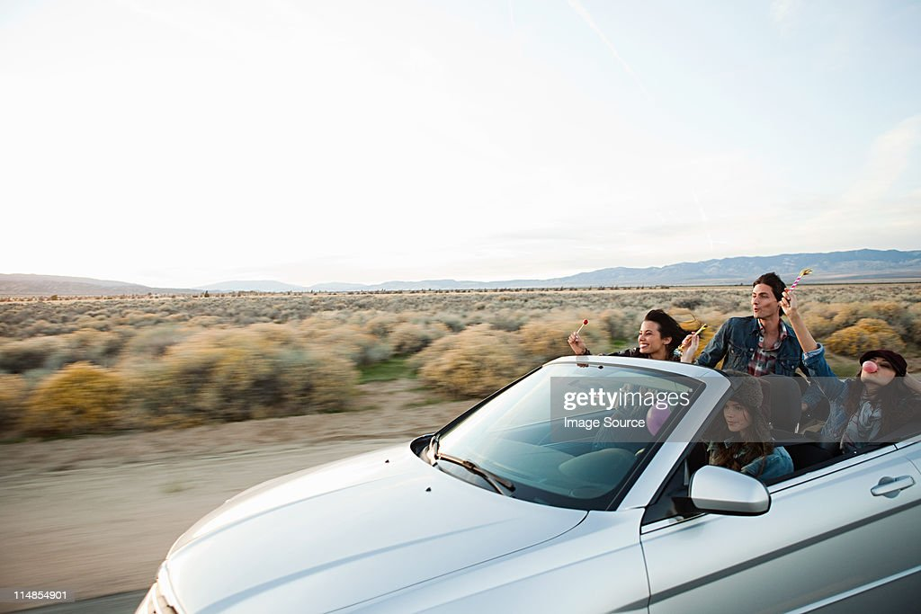 Four young friends in convertible car : Stock Photo