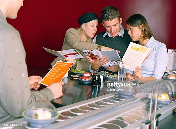 four young friends in sushi restaurant, selecting food from menu - sushi restaurant stock photos and pictures