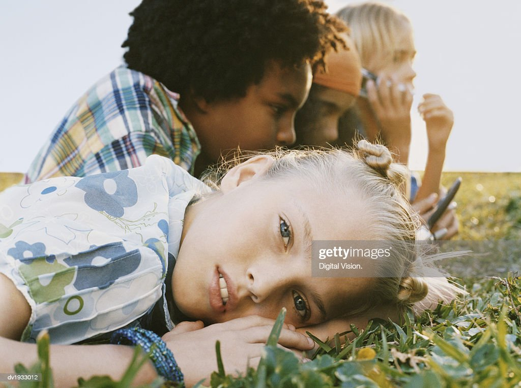 Four Young Friends Lying on Grass, with One Girl Looking at the Camera : Stock Photo