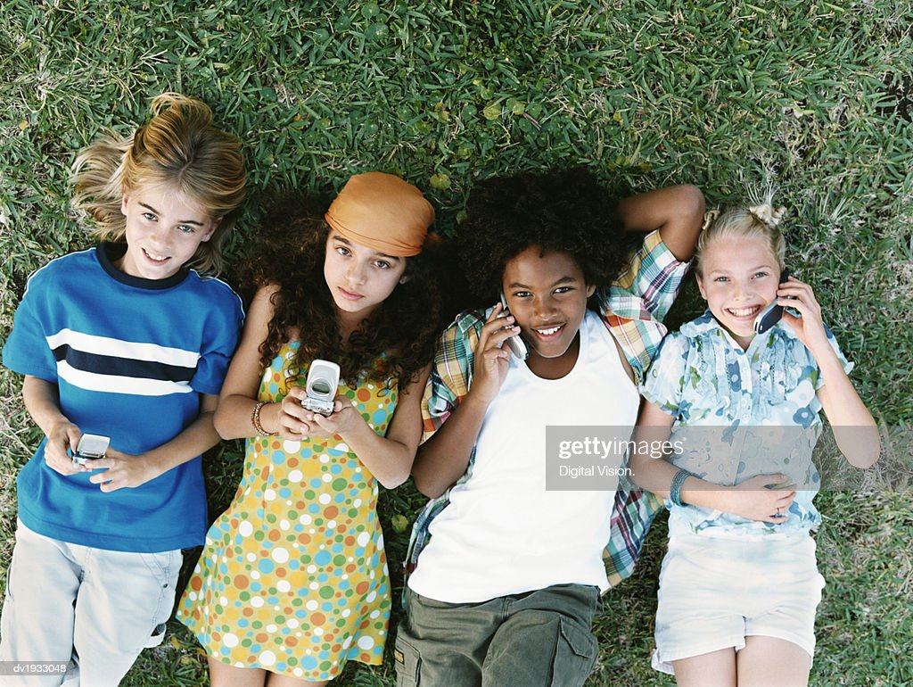 Four Young Friends Lying Together on Grass, Using Mobile Phones : Stock Photo