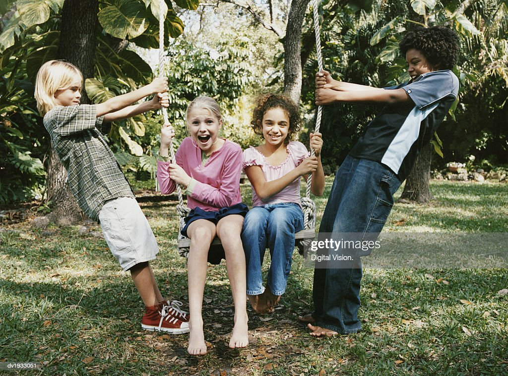 Four Young Friends Messing About on a Swing : Stock Photo