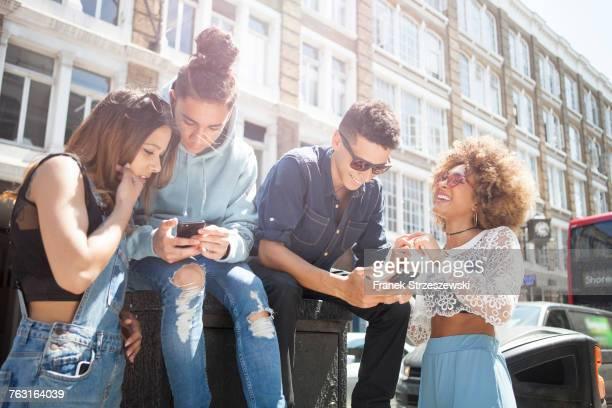 Four young friends outdoors, looking at smartphone