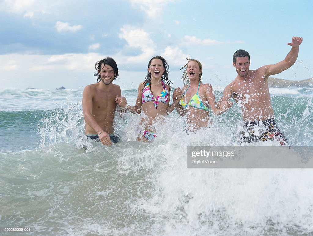 Four young friends splashing in sea, portrait : Stock Photo