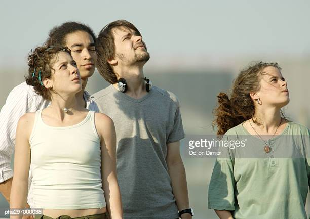four young friends standing, looking up at sky - number of people stock pictures, royalty-free photos & images