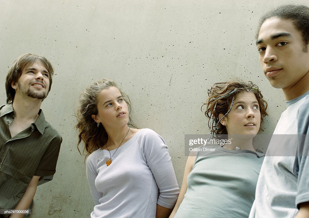 Four young friends standing next to wall : Stockfoto