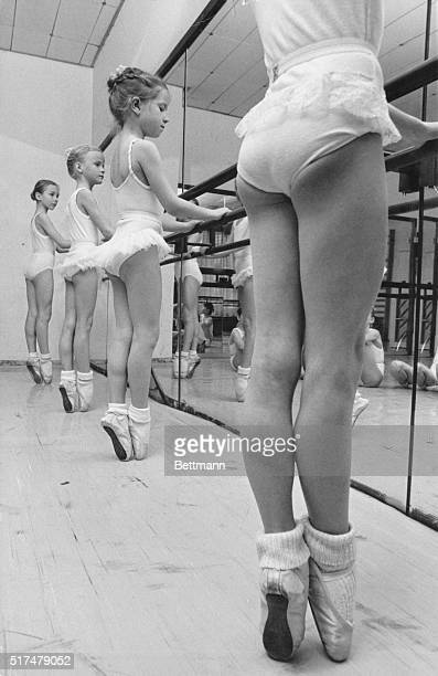 Four young girls on point check their positioning at the bar in ballet class