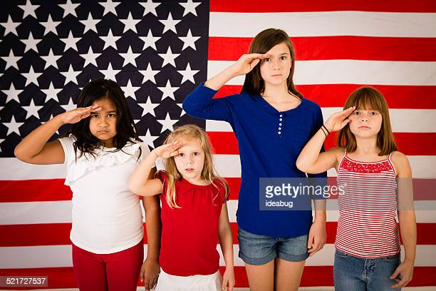 Four Young Girls Saluting in Front of American Flag