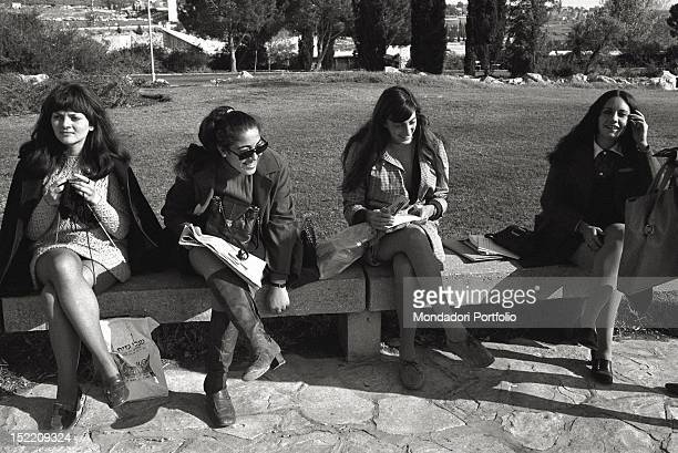 Four young Israeli girls passing the time reading books and newspapers or knitting seated on a bench in a garden in Jerusalem they are fashionably...