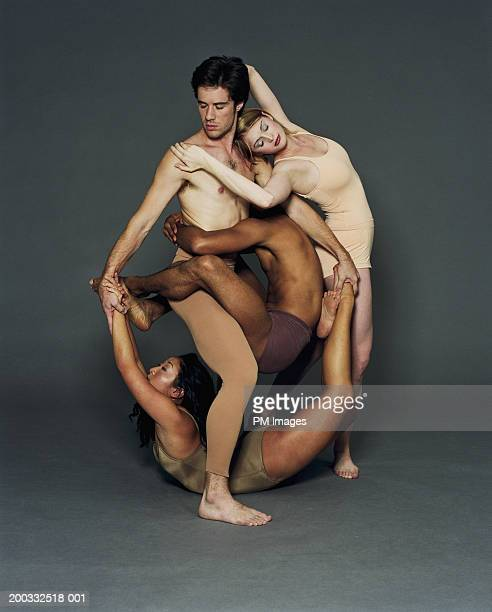 Four young male and female modern dancers in circular pose