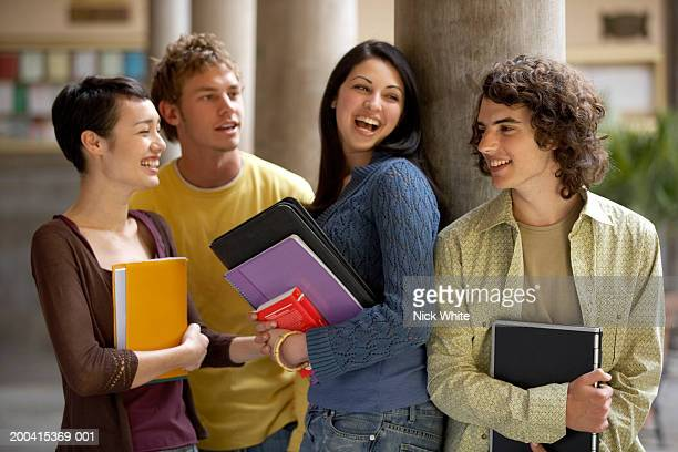 Four young male and female students standing in colonnade, smiling