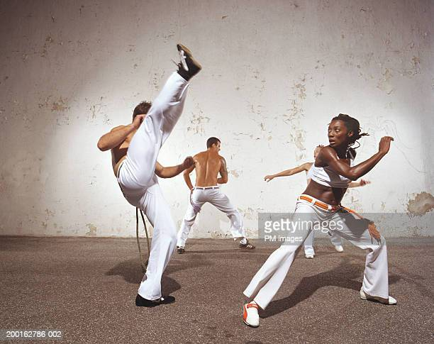 Four young men and women practicing Capoeira, side view