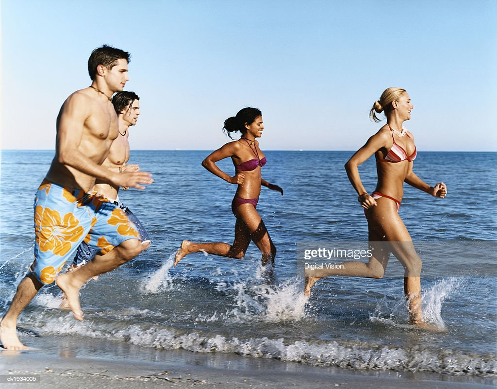 Four Young Men and Women Run on the Beach at the Water's Edge : Stock Photo