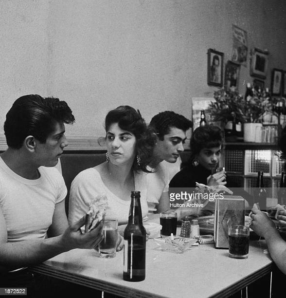 Four young men and women sit in a booth talking while eating a meal inside a diner 1950s