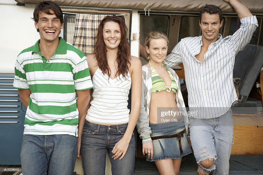 Four Young Men and Women Standing in Front of a Motor Home : Stock Photo