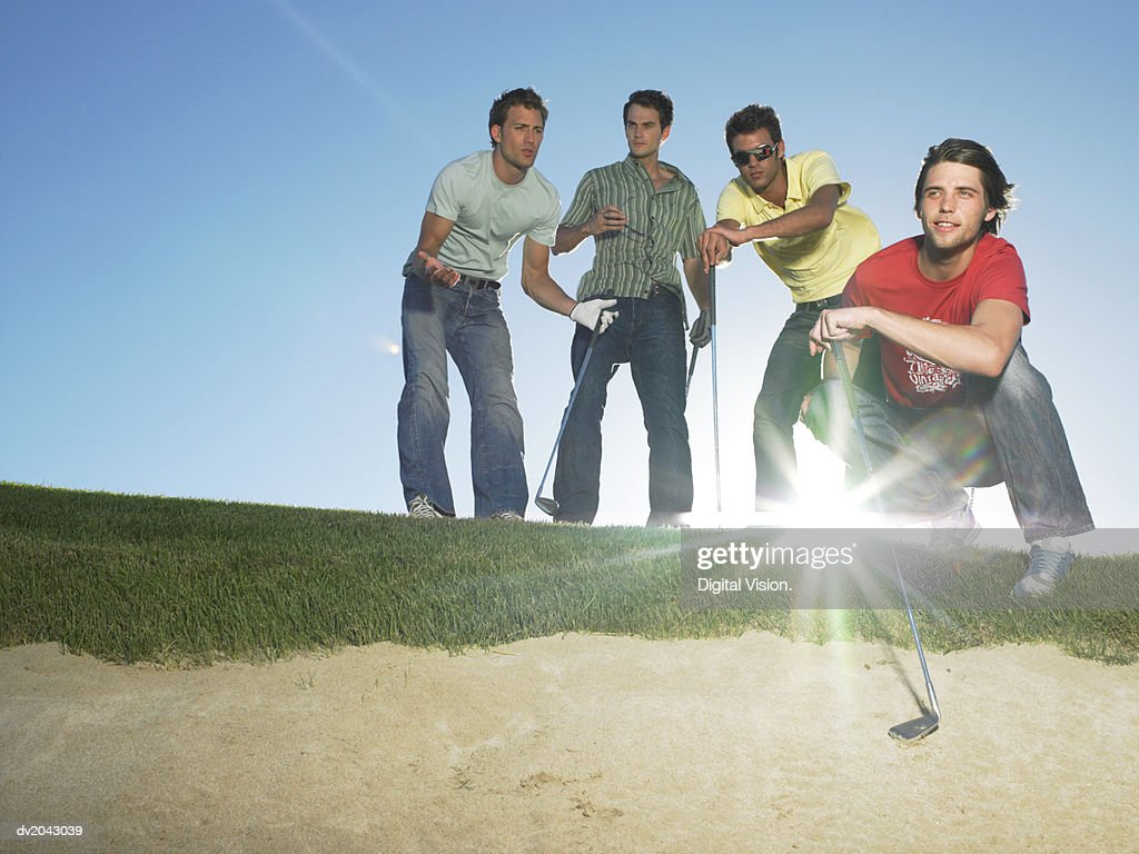 Four Young Men at the Edge of a Sand Bunker Holding Golf Clubs : Stock Photo
