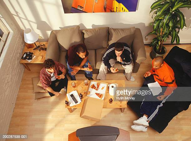 Four young men eating pizza watching television in flat, elevated view