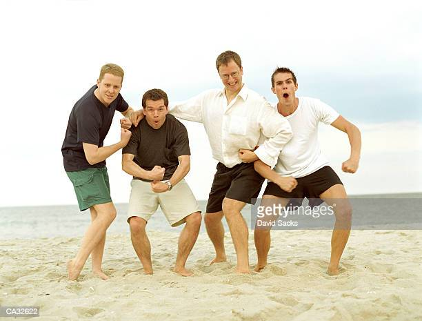 Four young men flexing muscles on beach, portrait