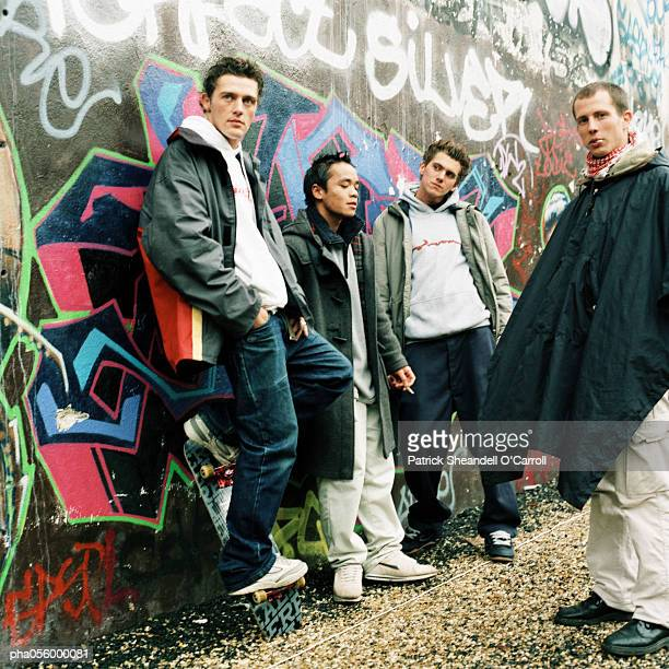 four young men in city street, three leaning back against graffiti wall - gang stock pictures, royalty-free photos & images
