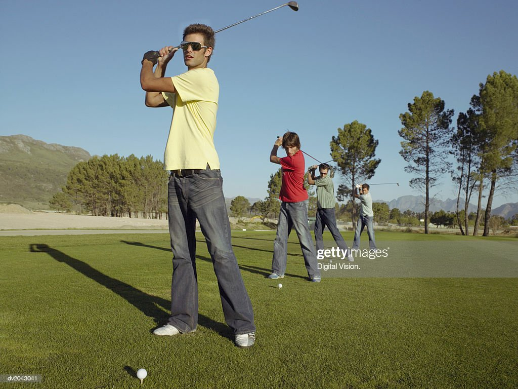 Four Young Men Playing Golf on a Golf Course : Stock Photo