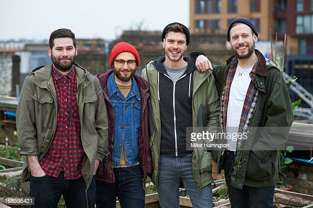 four young men smiling straight to camera. - four people stock pictures, royalty-free photos & images