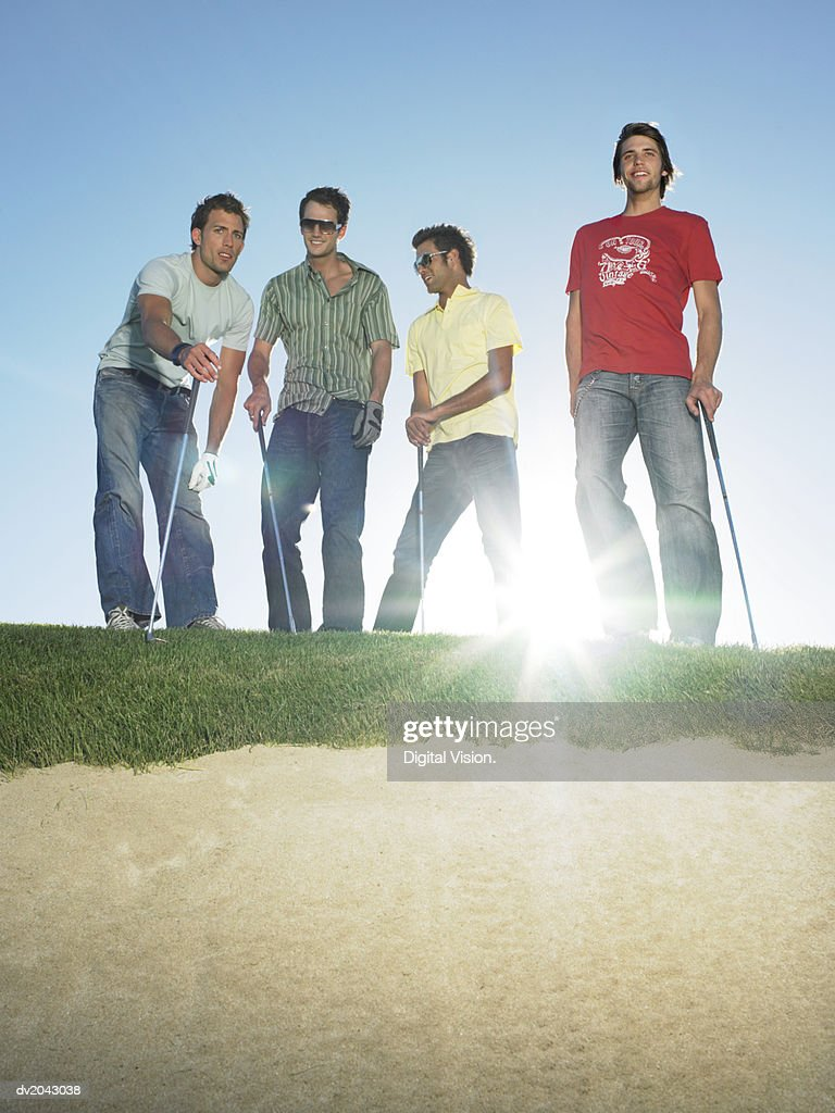 Four Young Men Standing at the Edge of a Sand Bunker Holding Golf Clubs : Stock Photo