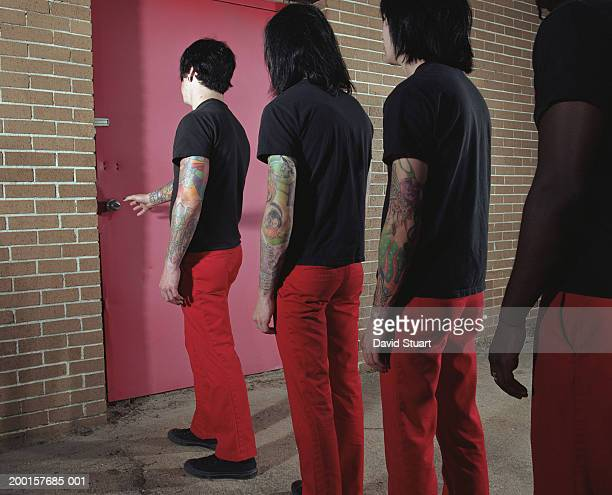 Four young men standing in line outside door, rear view