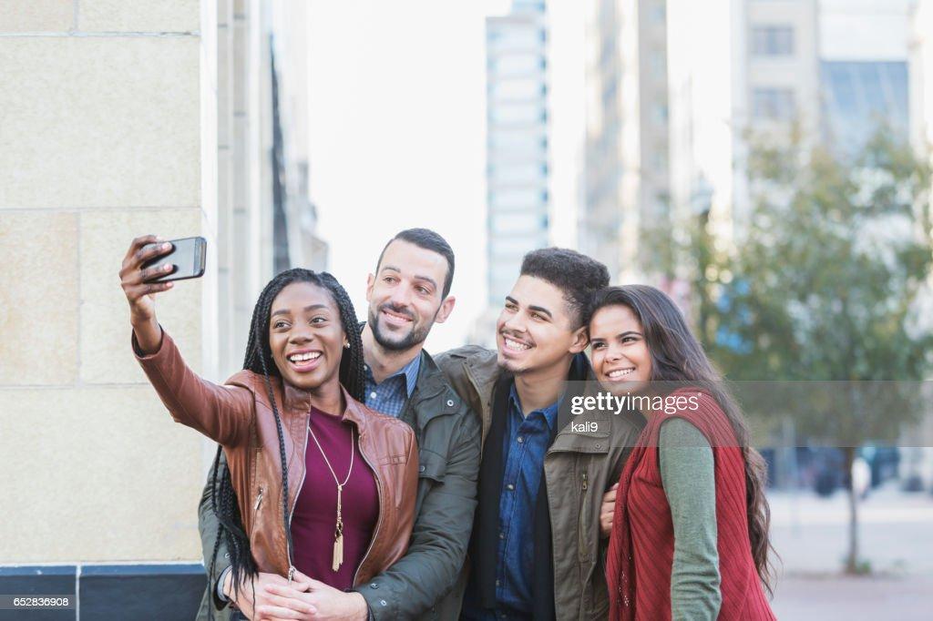 Vier jonge multi-etnische volwassenen selfie te nemen in de stad : Stockfoto