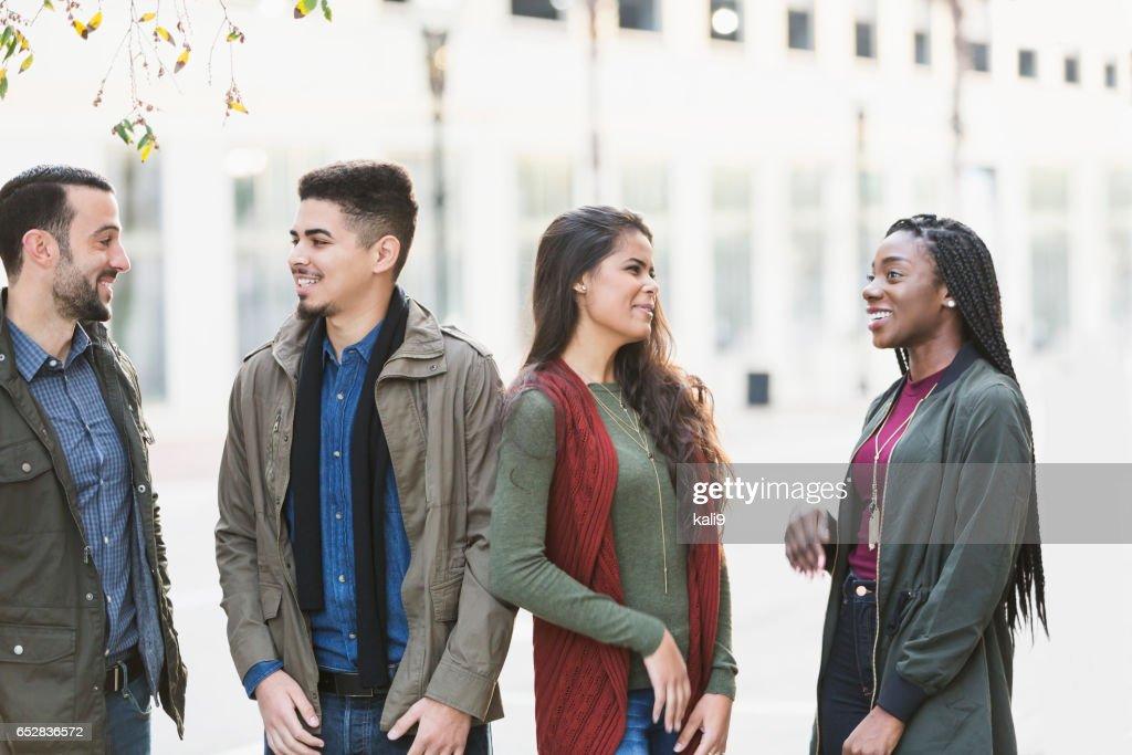 Quatre jeunes adultes multiethniques parlant bâtiment extérieur : Photo