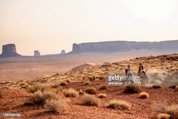 four young native american navajo brothers and sisters riding their horses bareback in the northern arizona monument valley tribal park at dusk together - apache stock pictures, royalty-free photos & images