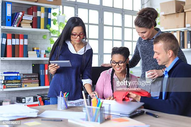 Four young people discussing ideas in modern office