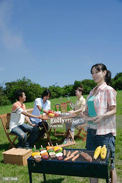 Four young people enjoying barbecue