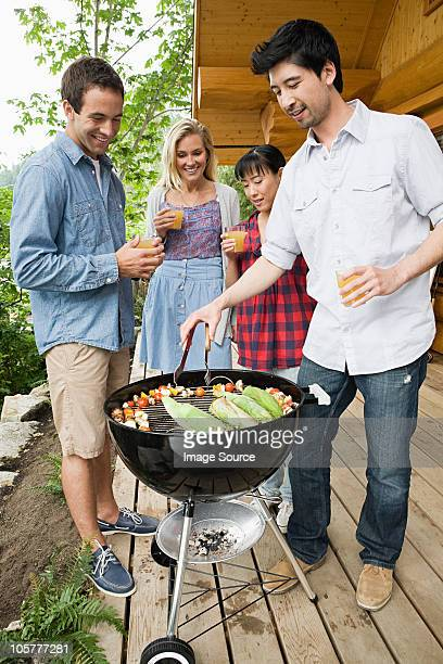 Four young people having a barbecue