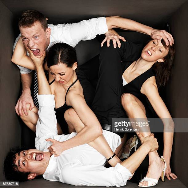 four young people in black room - confined space stock pictures, royalty-free photos & images