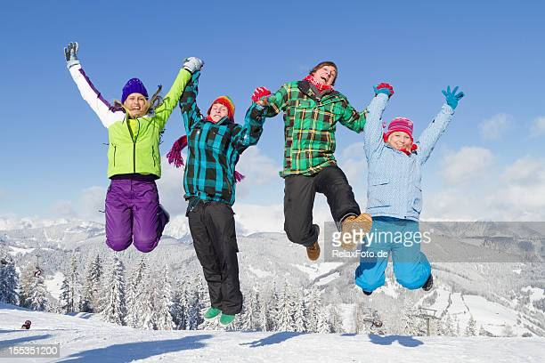 Four young people in multi colored clothes jumping on snow