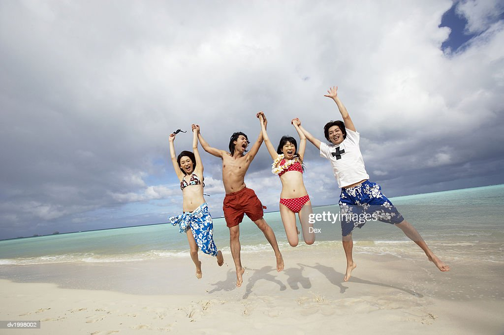 Four Young People in Swimwear Holding Hands on the Beach, Jumping in the Air and Shouting : Stock Photo
