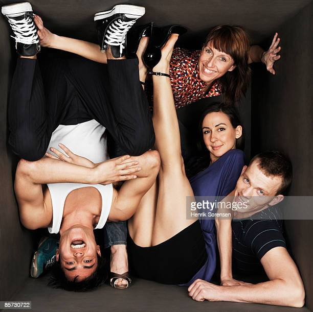 four young people inside a small black room - trapped stock pictures, royalty-free photos & images