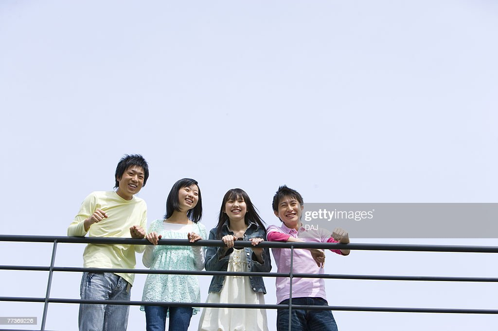 Four young people leaning on the railing, side by side, low angle view, blue background, copy space, Japan : Stock-Foto
