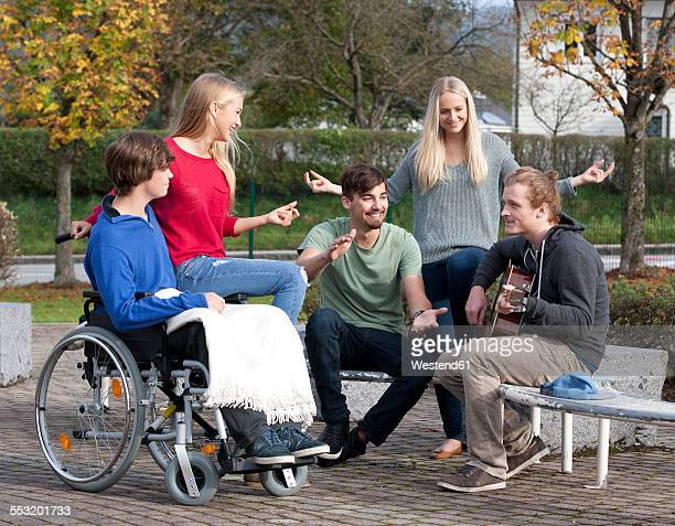 Four young people listening guitarist