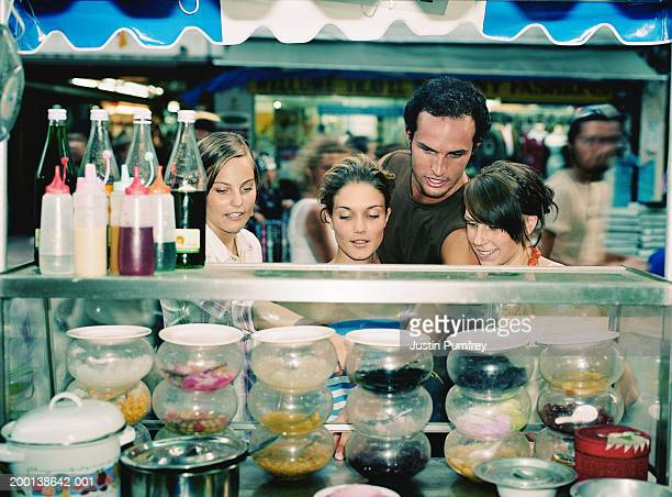 four young people looking at selection of food in glass counter - nur erwachsene stock-fotos und bilder