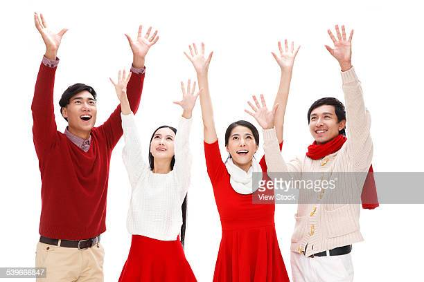 Four young people looking up with arm raised above
