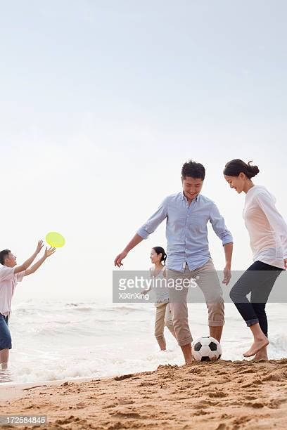 Four young people playing soccer and Frisbee on the beach, China