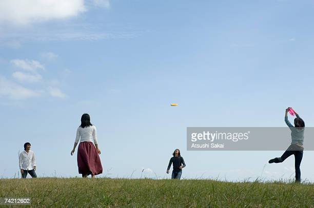 Four young people playing with flying disc
