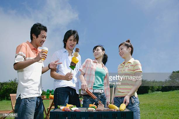 Four young people preparing barbecue