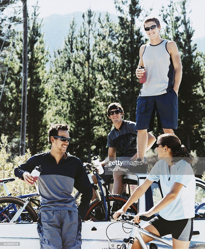 Four Young People Relaxing by an Off Road Vehicle With Their Mountain Bikes : Stock Photo