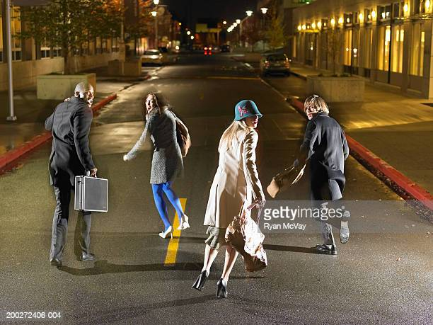 Four young people running down road, looking over shoulders, rear view