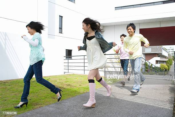 Four young people running in campus, front view, side view, Japan