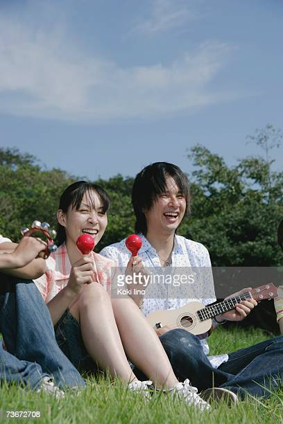 Four young people singing on grass field